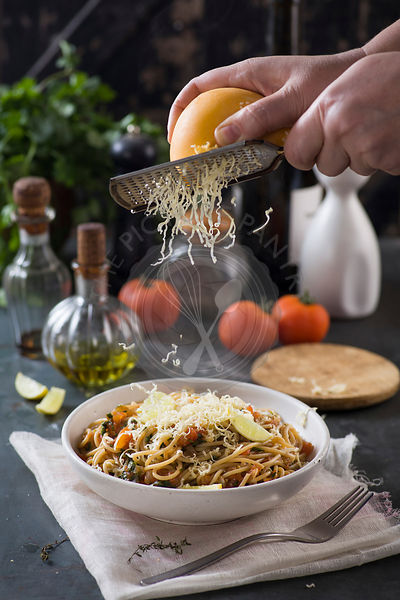cheese grated over spaghetti with tomato sauce and herbs