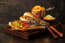 Burger with chicken breast and fried onions with coleslaw and potato wedges on dark background