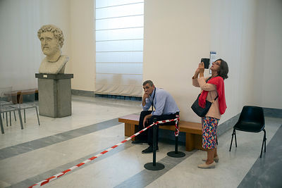 A woman takes a photograph whilst a bored guard rests in the National Archaeological Museum in Naples