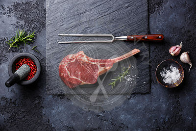 Raw fresh meat Veal rib Steak on bone and seasonings on dark background