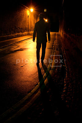 An atmospheric image of the silhouette of a mystery man, walking in a dark street at night.