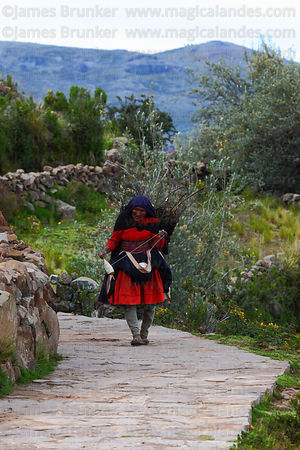 Old Quechua lady wearing traditional dress spinning wool as she walks , Taquile Island , Peru