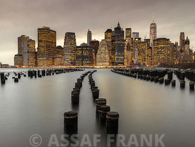 Manhattan skyline with rows of groynes in East river, New York