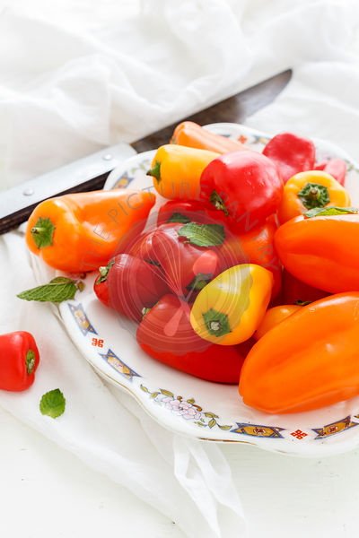 Sweet Crunchy Colorful Peppers on a plate on white background