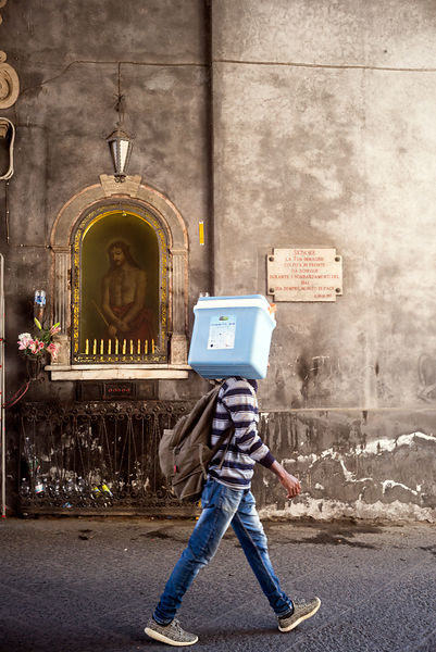 A man carrying a coolbox walks past a Christian shrine by the Piazza del Duomo in Catania