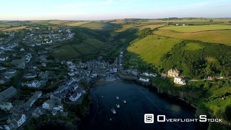 Drone tracks sideways over the village of Port Isaac in Cornwall as the early morning sun lights the local cointryside