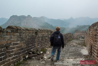 Tourist walking on the Great Wall in a misty morning
