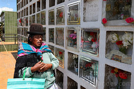Aymara woman saying prayers for souls of the dead in cemetery during Todos Santos festival, La Paz, Bolivia