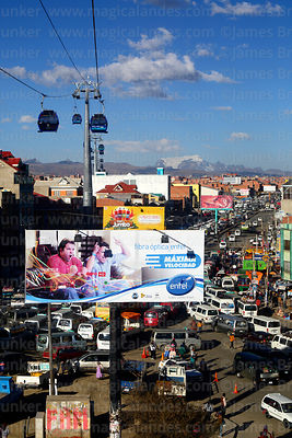 Blue Line cable car cabins above traffic jams and hoarding in Rio Seco, El Alto, Bolivia