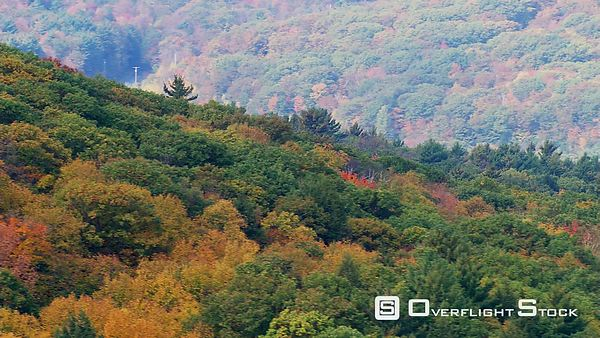 Flying over hills splotched with fall foliage, passenger POV