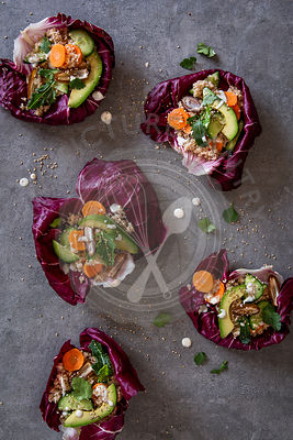 Radicchio bowls with couscous and vegetables over grey concrete background