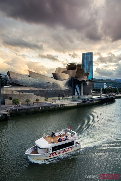 Guggenheim museum and river with boat, Bilbao, Spain