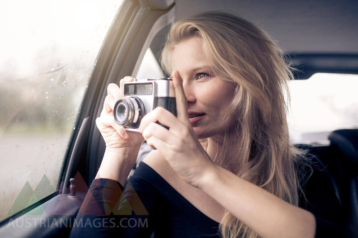 Woman sitting in car taking picture with camera