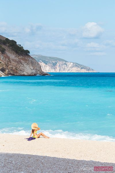Woman sitting near the sea on Myrtos beach. Kefalonia, Greek Islands, Greece