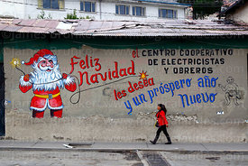 Woman walking past Father Christmas mural on wall of the offices of an electricians and electrical workers cooperative, La Pa...