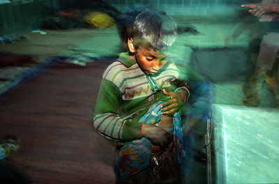 India - Delhi - A boy at a night shelter in Old Delhi for street children, scratches his flea bites