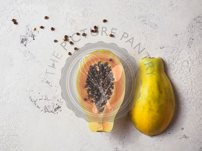 Papaya cut in half with seeds scattered around on a white textured surface.