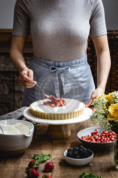 Adding fruit to the top of a mascarpone and strawberry tart