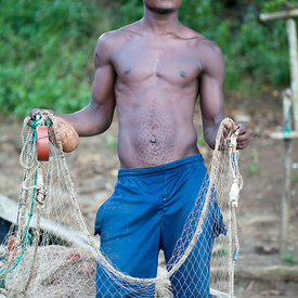 Fisherman mending his nets, near Praio Milao, Sao Tome