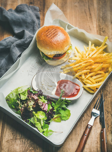 Beef burger, french fries, salad and sauces on tray