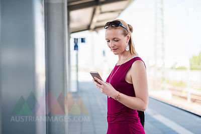 Smiling mature woman standing on platform looking at cell phone