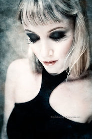 Blond woman with dark eyelashes and shadow in a black halter top.