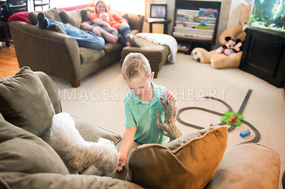 Male child feeding his dog on couch