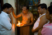 The family priest gives a blessing to Radakrishna and Srikanda Stpathy and their wives in the family shrine in the Stapathy h...