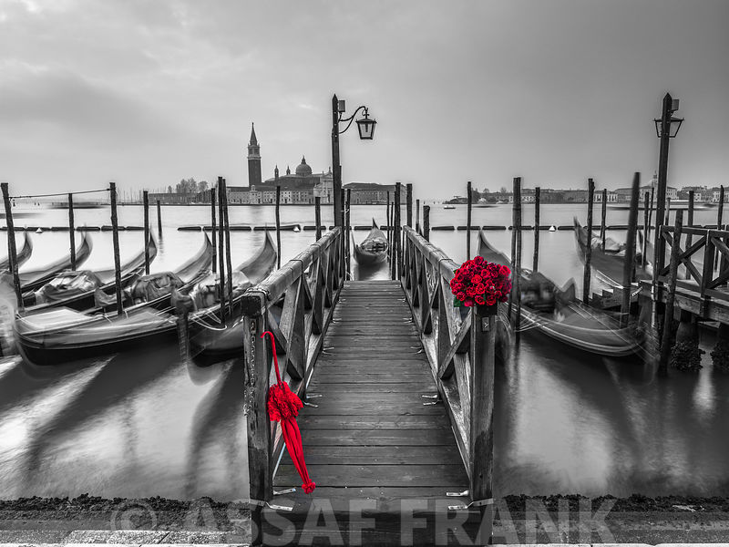 Bunch of Roses and umbrella on pier with gondolas moored in canal, Venice, Italy