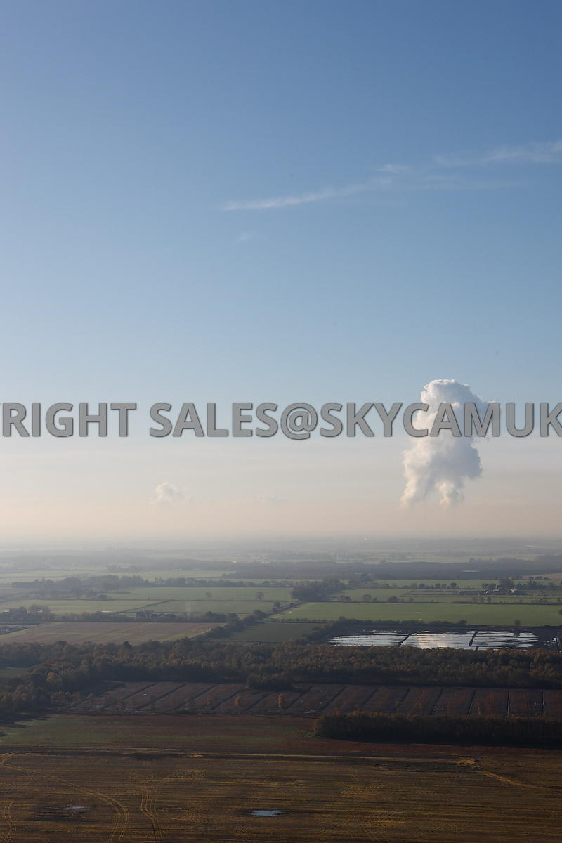 Aerial photograph of farmland with Fiddlers Ferry power station  on the horizon with steam plumes rising above the station se...
