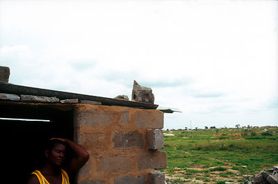 Angola - Luanda - A woman stands in the ruins of her house