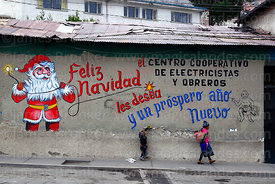 Children walking past Father Christmas mural on wall of the offices of an electricians and electrical workers cooperative, La...