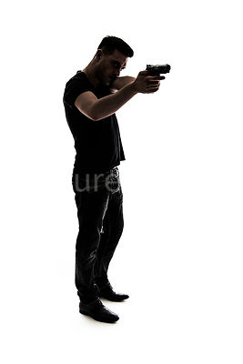 A mystery man, in silhouette, pointing a gun – shot from eye level.