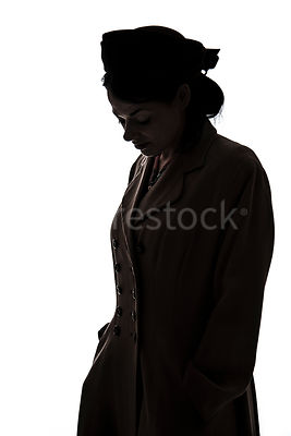 A silhouette of a 1940's mystery woman in a hat and coat, looking down – shot from mid-level.