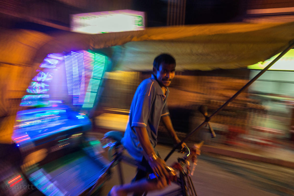 Rickshaw driver with and LED emblazoned rickshaw at night, Jodhpur Park, Kolkata, India