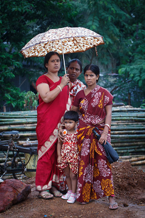 Mother and daughters in monsoon rains, Alipore, Kolkata, India