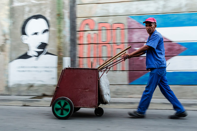 Street Sweeper Walking in Front of Mural of Cuban Flag