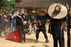 chus (masked old men figures) riding wooden horse during festival parade, San Ignacio de Moxos, Bolivia