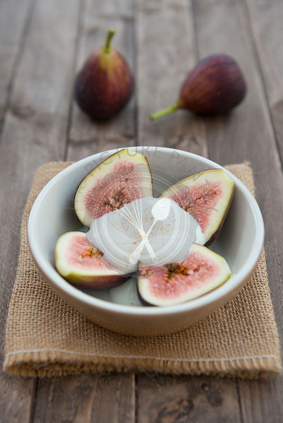 Figs in a bowl with natural yoghurt on a wooden background.
