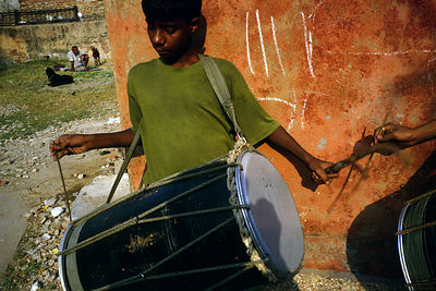 India - New Delhi - A boy practices his tabla drum in the street, Shadipur Depot