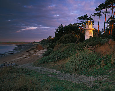 Yellow shafts of first sunlight on the Millennium Beacon, pine trees and  and distant shoreline at Lepe whilst a interesting ...