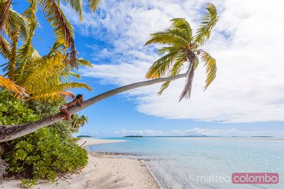 Woman on a palm tree on tropical beach