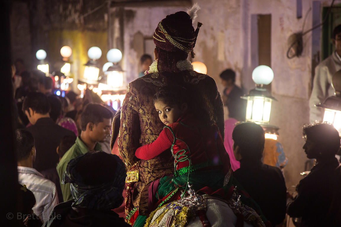 A groom and his daughter ride a horse in a marriage procession at night, Pushkar, Rajasthan, India