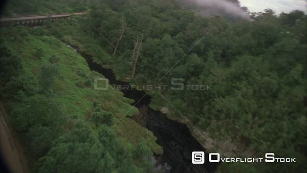 Aerial shot over a river cutting through lush green forest and landscape and passing over a bridge. Eastern Cape South Africa