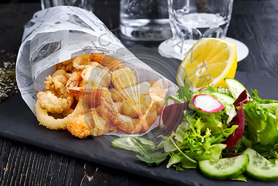 Fried shrimps in paper cone on plate with vegetable salad