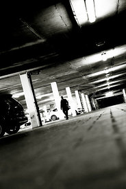 An atmospheric image of a mystery man walking through a dark, empty car park.