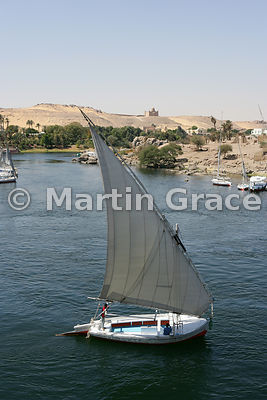 A felucca (traditional sailing vessel) on the River Nile at Aswan, Egypt, with the Aga Khan Mausoleum beyond