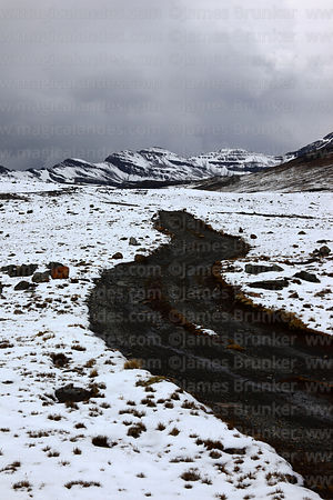 Track across puna grassland towards Mt Charkini after winter snowfall, Cordillera Real, Bolivia