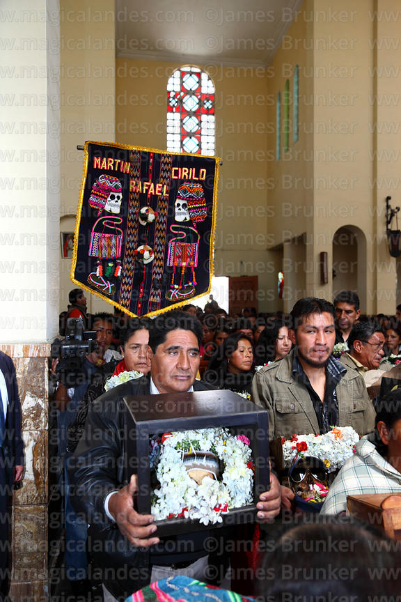 Devotees with banner of their skull worshipping society in church during mass, Ñatitas festival, La Paz, Bolivia