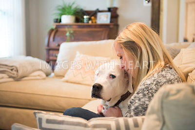 Female human and white dog snuggling on couch
